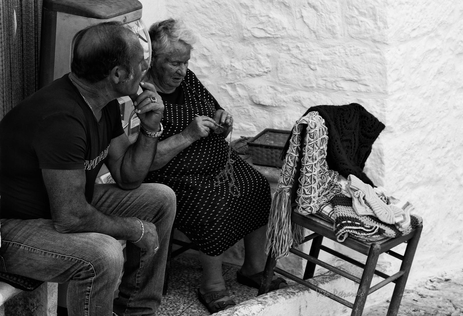 Donna che ricama e cuce tra i trulli